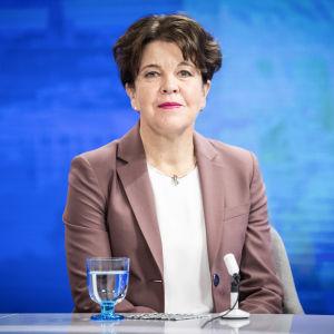 Mörkhårig kostymklädd sittande kvinna mot en blå bakgrund. Chefen för Europeiska kompetenscentret för motverkande av hybridhot Teija Tiilikainen i Yles studio i september 2020.