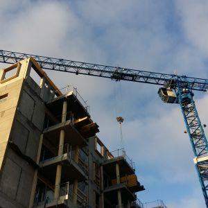 En blå lyftkran lyfter upp byggmaterial till ett flervåningshusbygge.