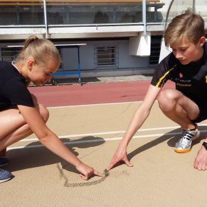 Elsa Karjalainen och Riku Uusitalo, som tränar friidrott med TuUL, känner på groparna i löpbanan.