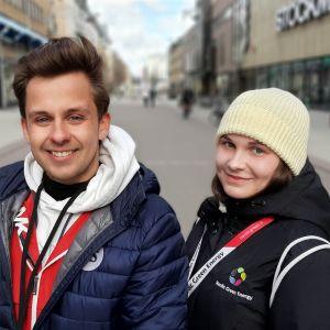 En ung man och en ung kvinna tittar in i kameran och ler. De står på en tom gågata.
