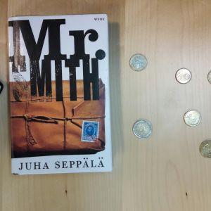 Juha Seppälän teos Mr. Smith pöydällä. Ympärillä kolikoita.