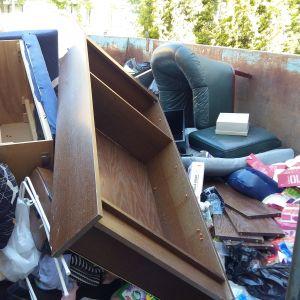 En soffa, en länstol och mycket skräp slängda på en sopcontainer efter att någon flyttat ut.
