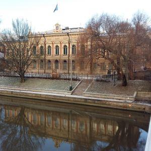 Åbo stadshus med Åbos blå flagga i topp speglas i Aura å en vinterdag med rimfrost i gräset.