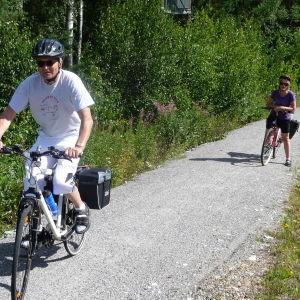 Två cyklister längs med en cykelväg av grus.