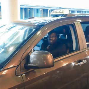 En man sitter i en taxibil. Han tittar in i kameran genom fönstret