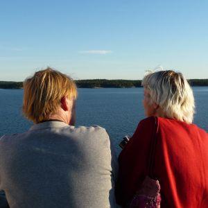 En man i grå tröja och en kvinna i röd tröja står på ett fartygsdäck och tittar ut över en stilla skärgård.