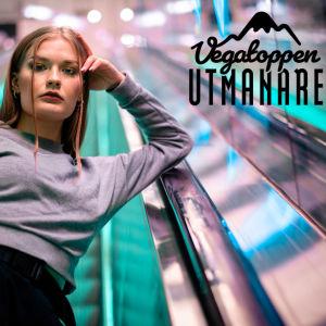 Artisten Dora Lagerspetz står i en rulltrappa.