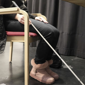 En kvinna sitter på en stol. Man ser inte hennes huvud. Hon har en vit käpp i handen.