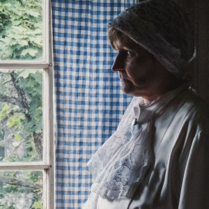 Kvinna i vit spetsklänning och vit klut på huvudet tittar ut genom fönster, som omgärdas av blåvitrutig gardin.