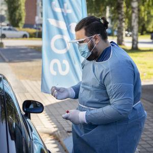 En man i skyddsutrustning utför ett coronatest på en person som sitter inne i sin bil. Patienten syns inte på bilden.