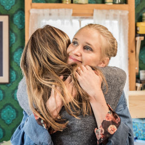 Lisa kramar en tjej hemma i vardagsrummet.