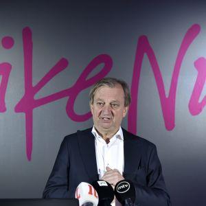 Hjallis Harkimo står framför en vägg med texten Liike Nyt.