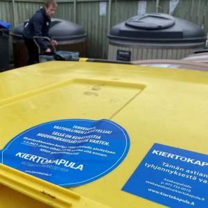 Keltaisessa muovinkierrätysastiassa on Kiertokaupulan logo