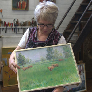 Kvinna håller i tavla med kor på.