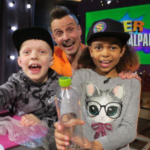 Superhjälparnas programledare Jontti Granbacka och två barn ler glatt, flickan håller upp en plastflaska mot tittaren
