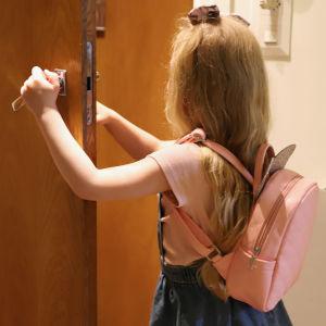 Pieni tyttö avaa ovea.