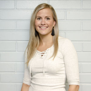 En blond kvinna iklädd en vit tröja, står framför en ljusgrå tegelvägg. Hon ler.