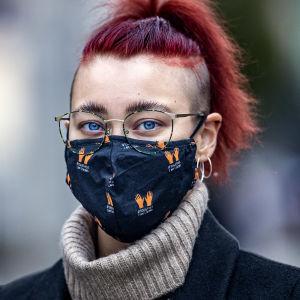 Profilbild på Jenna Turpeinen, som bär ett svart munskydd.