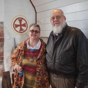 Nainen ja mies seisovat kirkon ikkunamaalauksen vieressä.