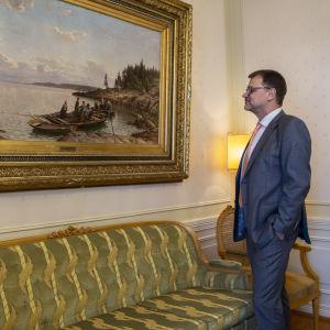 Juha Sipilä Hjalmar Munsterhjelmin maalauksen edessä.