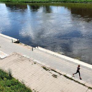 En joggare springer längs med floden Neris, som flyter genom Vilnius i Litauen.