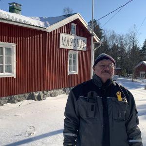 En man i vinterkläder står framför en gammal träbyggnad i snö.