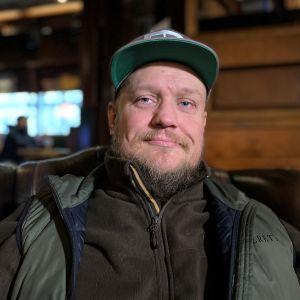 Ravintola Cherin yrittäjä Toni Yrjänne Lahdesta katsoo kameraa. Miehellä parta, lippis päässä.