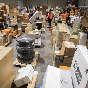 Mängder av paket saplade i en lagerhall.