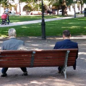 Två män sitter på en parkbänk i Helsingfors.