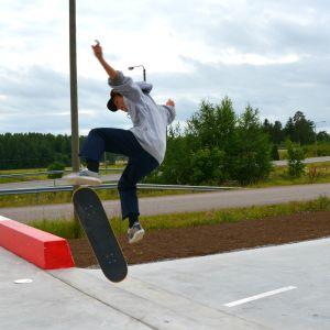 Ung pojke hoppar i luften från skateboard