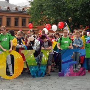 Stor folksamling i många färger med bokstäverna L O V E i olika färger. I bakgrunden Katedralskolan i Åbo