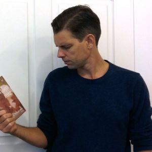 """Alex Schulman håller i boken """"Glöm mig""""."""
