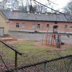 gårdshelhet med ett rött stenhus, ett gult rappat hus och ett hus av trä med lekpark för barn i mitten
