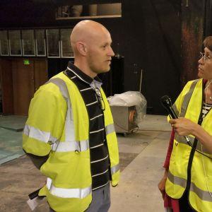 Bild av reporter Malin Hulkki med mikrofon i handen som intervjuar Wasa teaters marknadsföringschef Jan Fröjdö på teaterms scen.