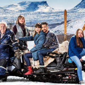 Perhe seisoo lumisessa tunturimaisemassa moottorikelkan ympärille kerääntyneenä.