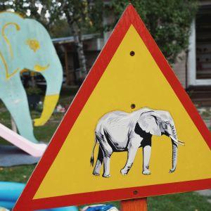 Varoituskolmio, jossa norsun kuva. Taustalla lasten leikkipaikka.
