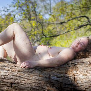 Monika Pensar naken på en trädstam. Hon har yllesockor på sig.