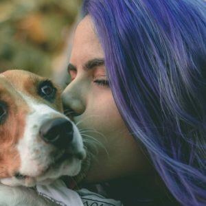 Nainen suutelee koiraa