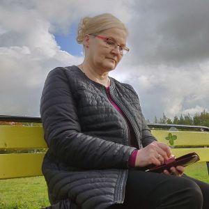 Aino Peltonen istumassa puiston penkillä.