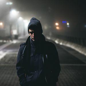Mies hämärällä kadulla.
