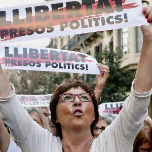 nainen pitää kylttiä, jossa vaaditaan poliittisten vankien vapauttamista.