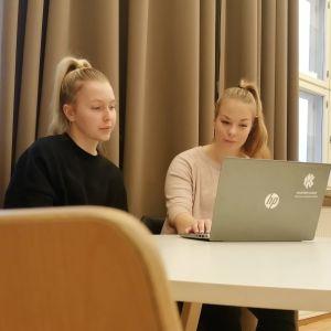 Aada Valtonen ja Tia Haikarinen tutkivat tietokonettta