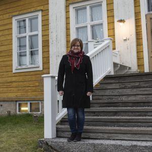 kvinna på trappa till gult hus