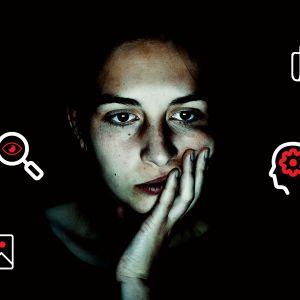 Kuvassa nainen katsoo tietokoneen ruutua, kuvassa musta tausta