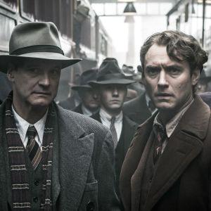 Colin Firth ja Jude Law mustavalkeassa kuvassa juna-asemalla