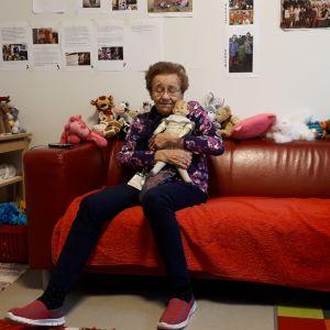 vanha nainen rutistaa nukkea sylissään punaisella sohvalla
