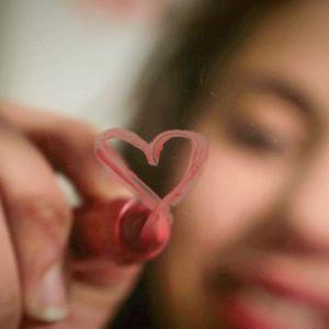 Tyttö piirtää huulipunalla sydäntä ikkunaan tai peiliin.