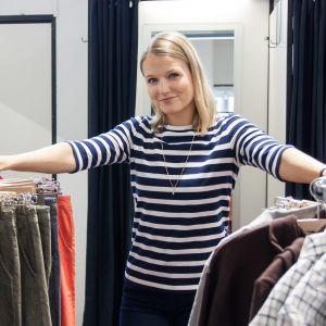 R-Collectionin pääsuunnittelija Lilli Norio nojaa vaatetelineisiin.