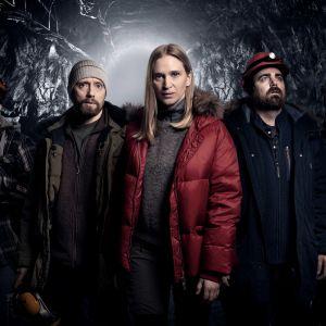 Viisi henkilöä talvivaatteet päällä pimeässä tunnelissa. White Wall -sarjan ohjelmakuva.