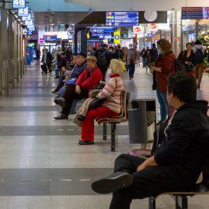 Kampin paikallisliikenteen terminaalissa odottaa ihmisiä penkeillä istuen.